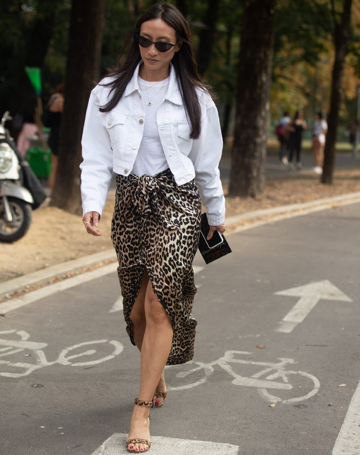 woman wearing a white denim jacket and leopard print skirt