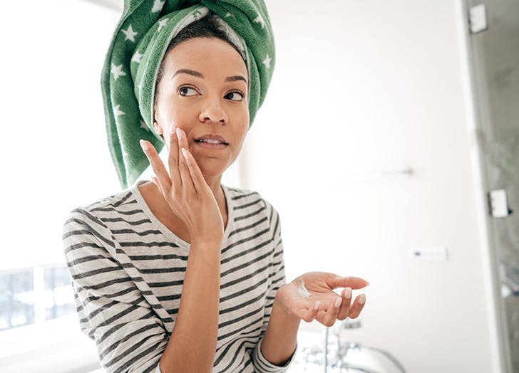 woman touching face in towel