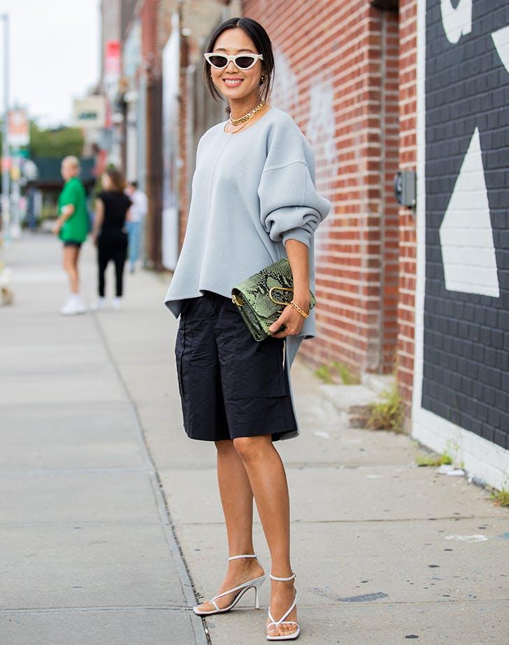 woman wearing long shorts and a sweatshirt