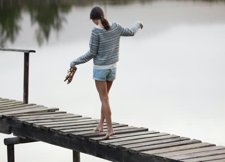 woman walking barefoot on a dock