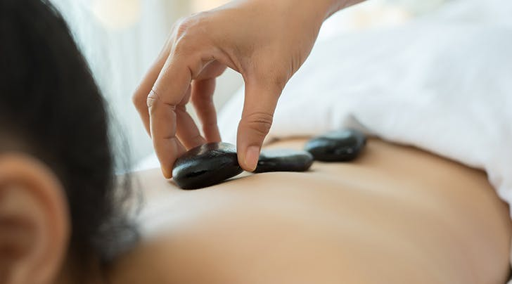 4 Hot Stone Massage Benefits That Totally Surprised Us (And 1 Important Reason to Skip Them)