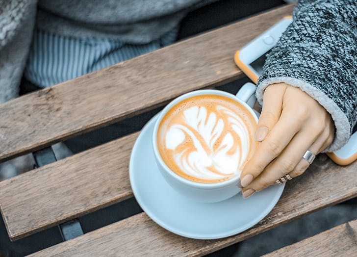 woman holding latte