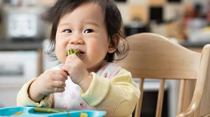 cute baby eating solids in chair