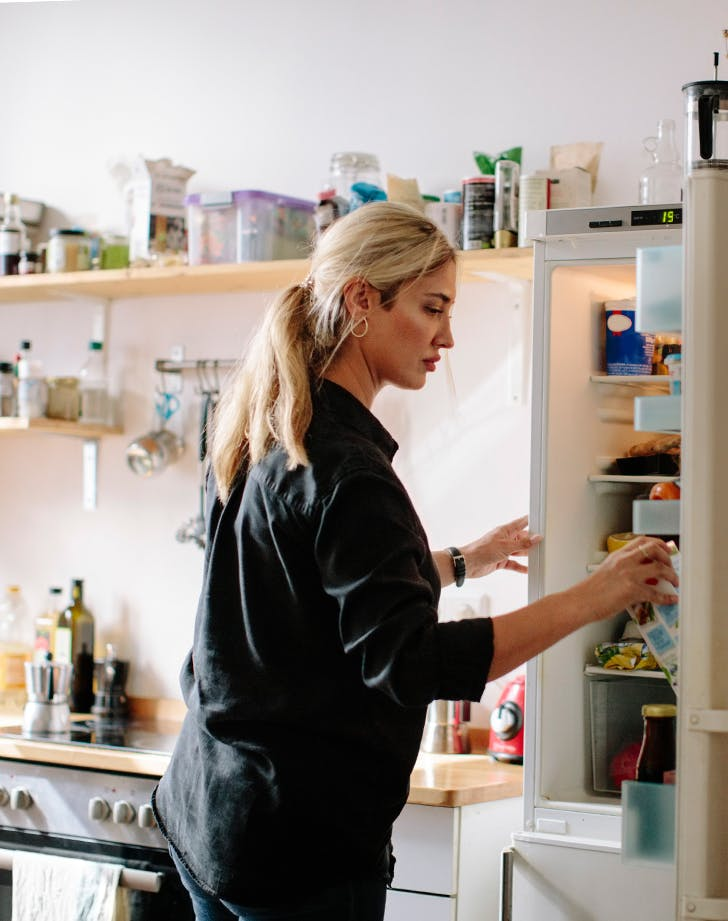 woman looking in her refridgerator