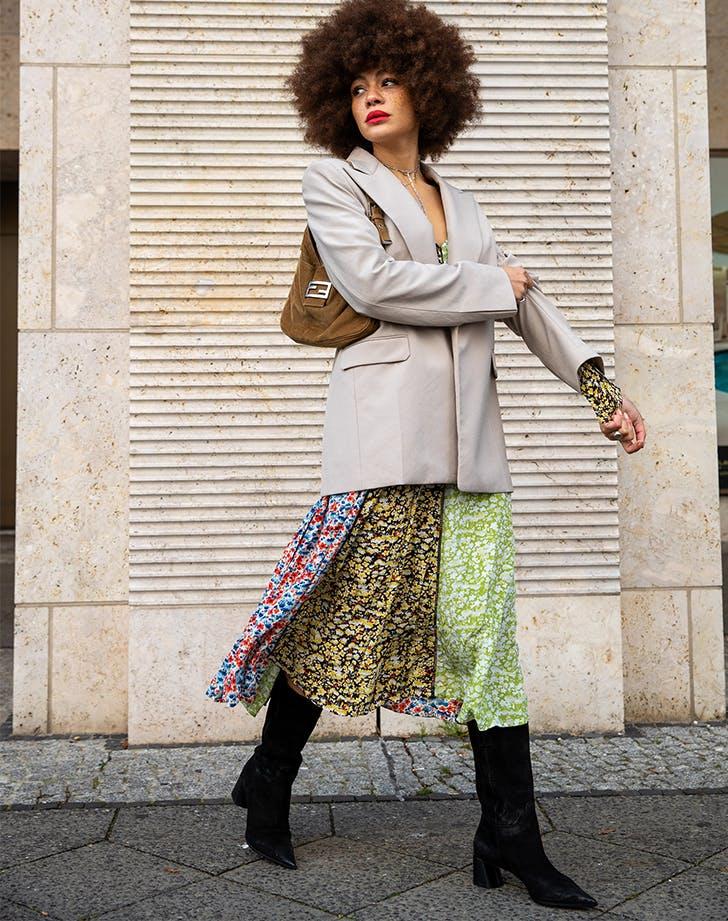 woman wearing a beige blazer and patterned dress