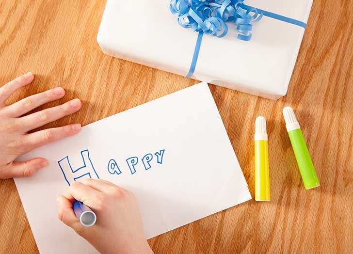 child writing birthday card