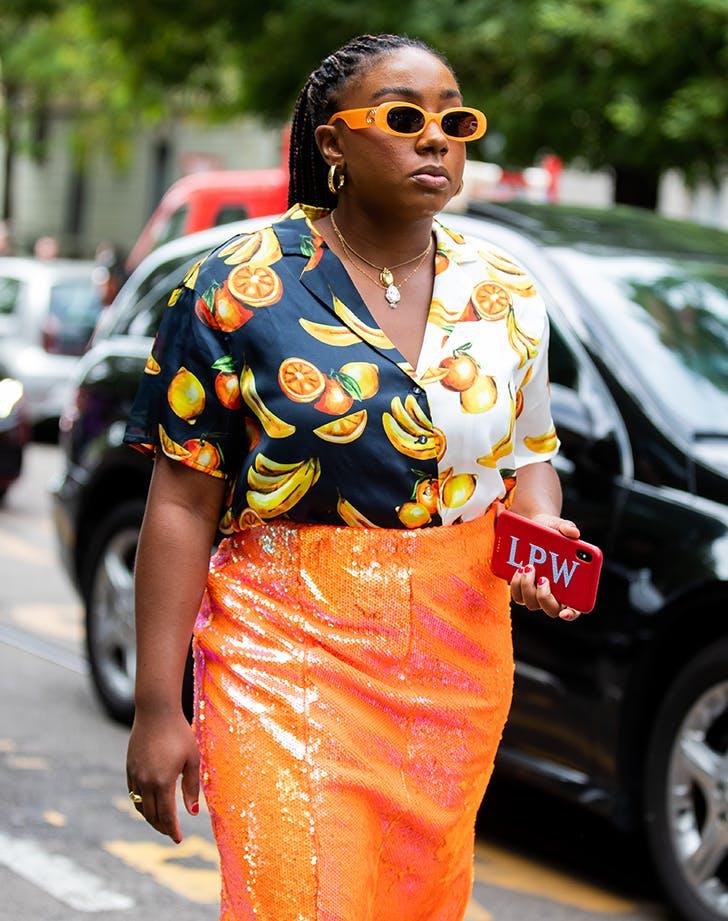 woman wearing a fruit print shirt and orange skirt