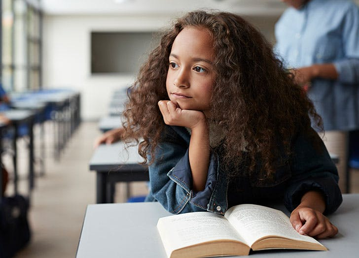 young girl thinking while reading