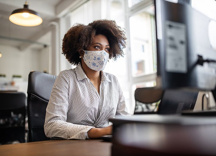 woman at computer with mask on at work cat