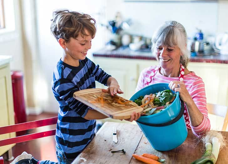 kid composting with grandmother