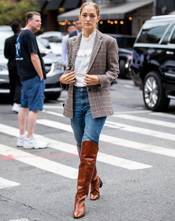 knee high boot outfits woman wearing an oversize blazer and jeans