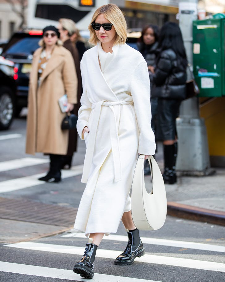 woman wearing black chelsea boots and a white coat